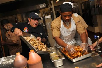 Celebrity chef shows how to prepare chicken wings for sailors at naval station